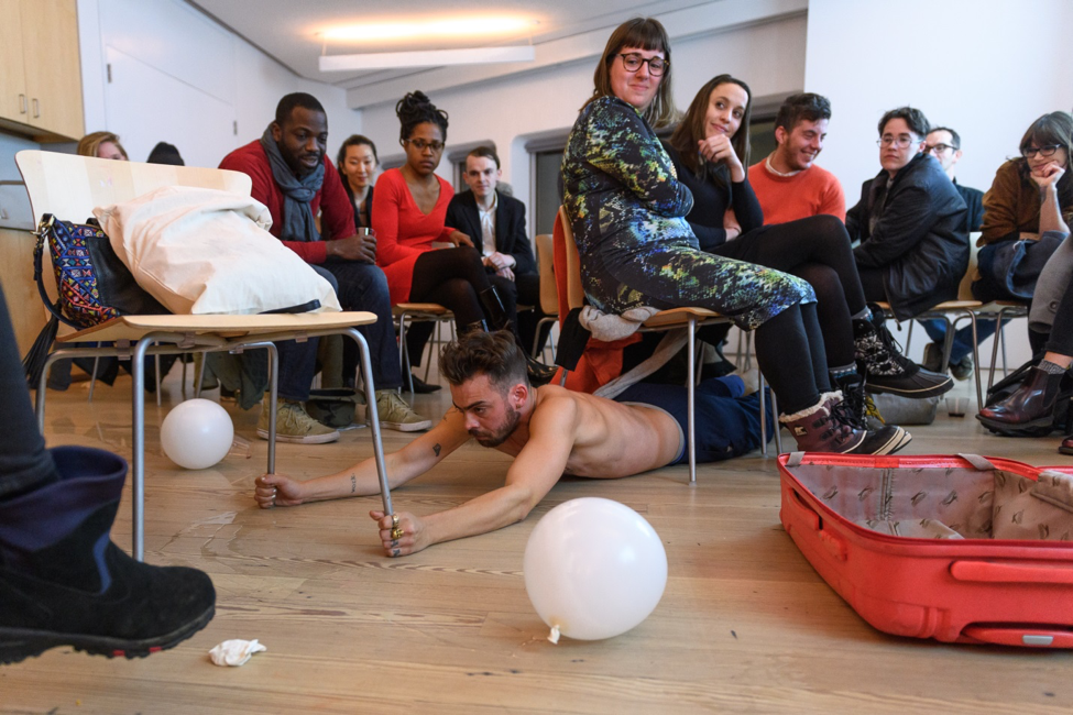 Artist Geo Wyeth performs in a room full of seated people.