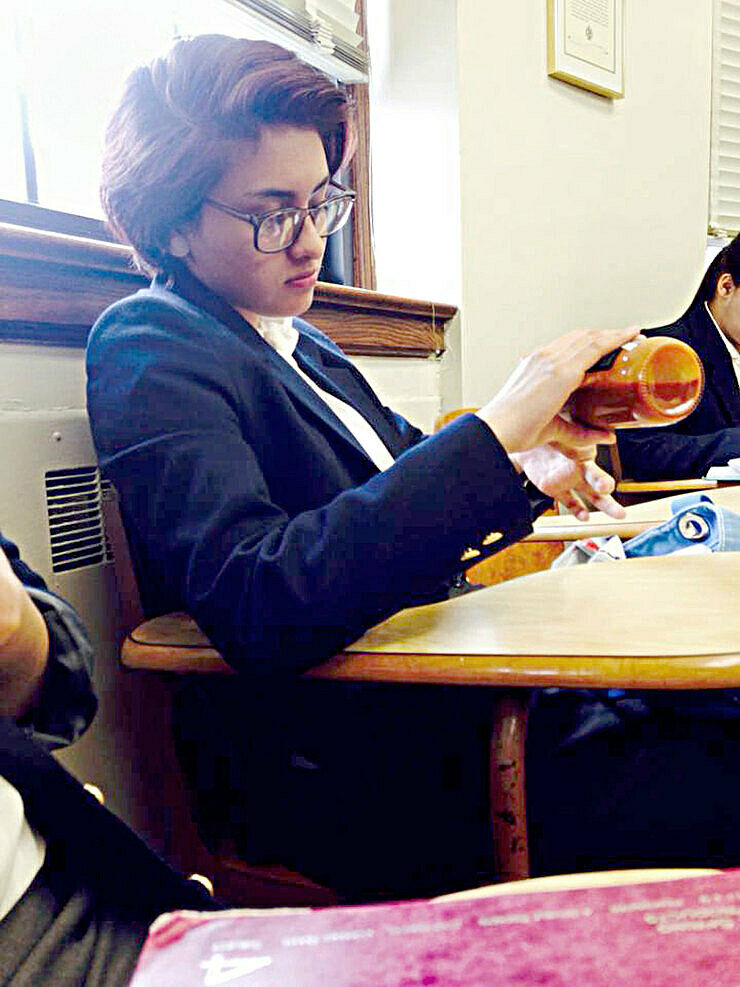 Teen artist Andrea sitting at a table.