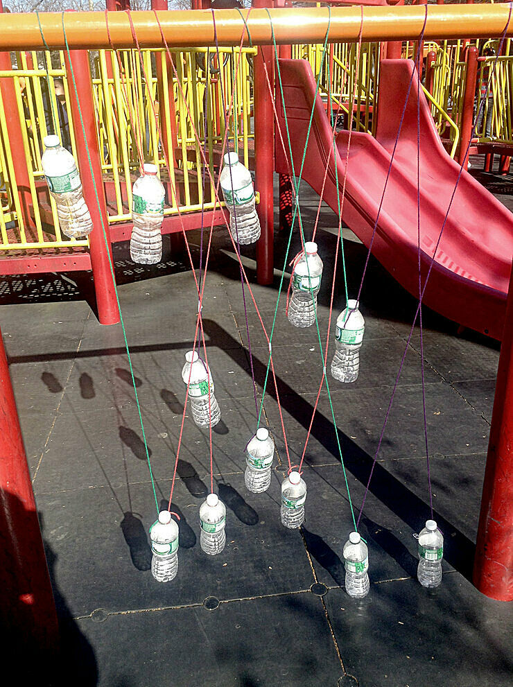 Artwork featuring water bottles hanging from string in a playground.