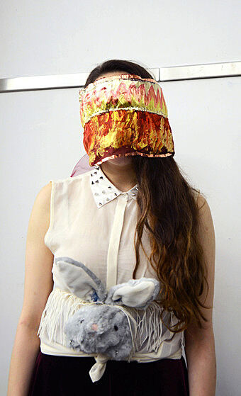 A teen wears a yellow and red mask.