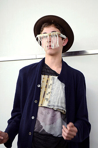 A teen artists wears glasses he made of fabric.