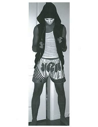 A teen artist wears a white mask and silver shorts.