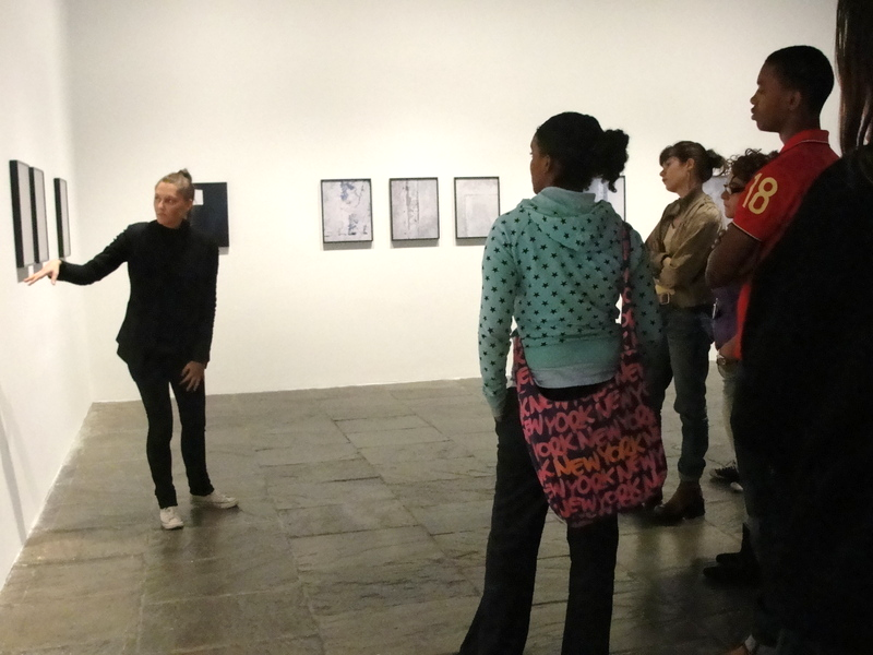 Sara VanDerBeek points to a painting in a gallery while students look on.