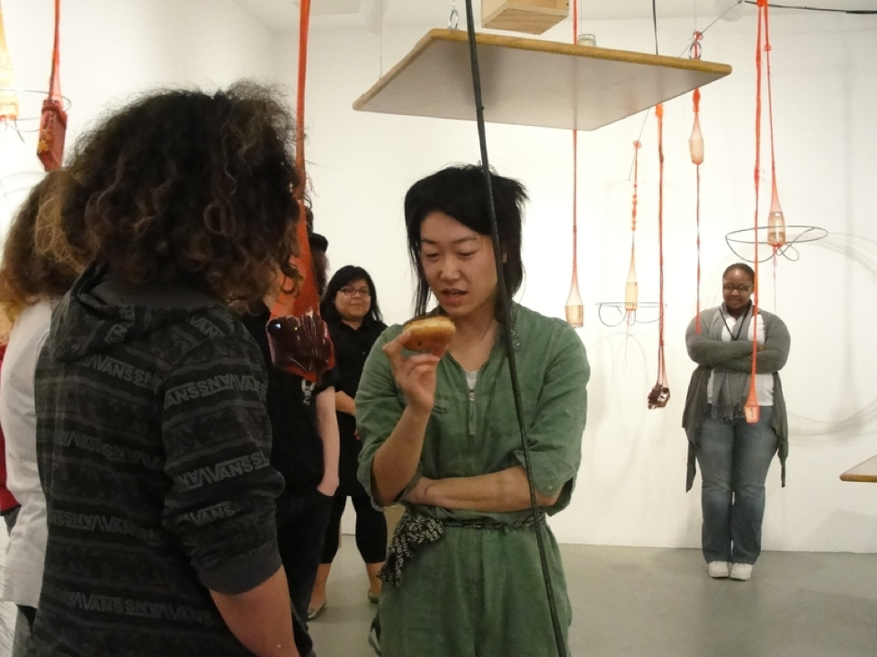 Artist Aki Sasamoto talks to students in a gallery.