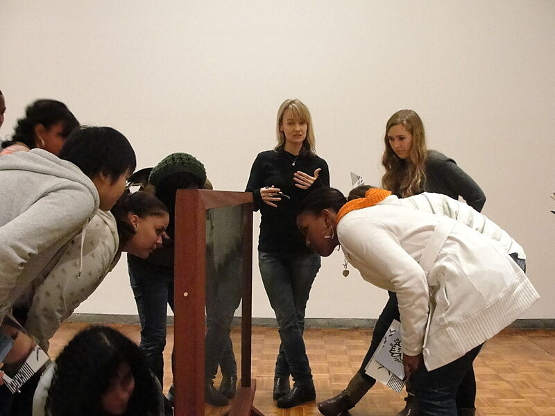Suzanne Bennett looks at a sculpture with students.