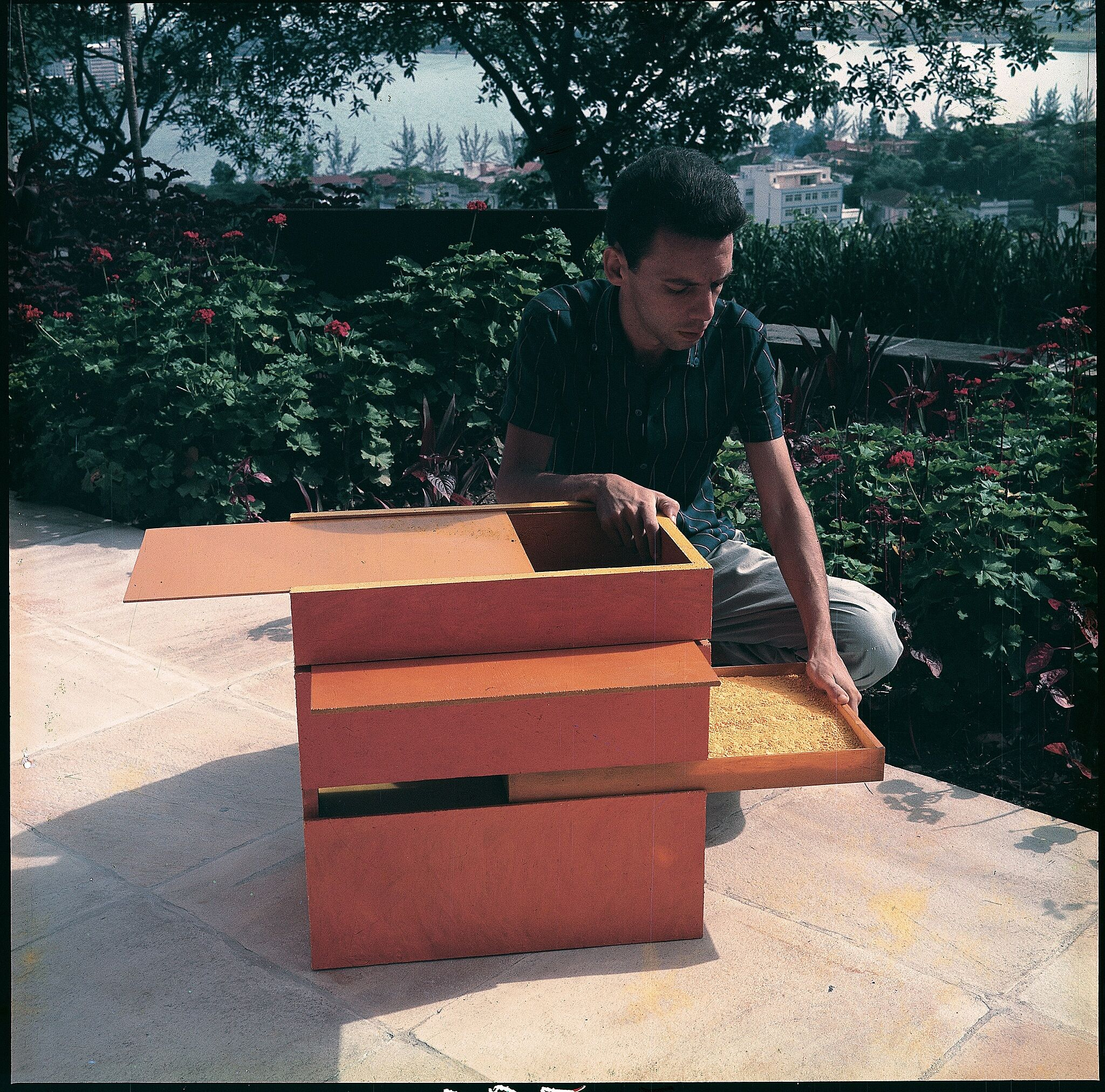Man interacting with wooden box with multiple openings.