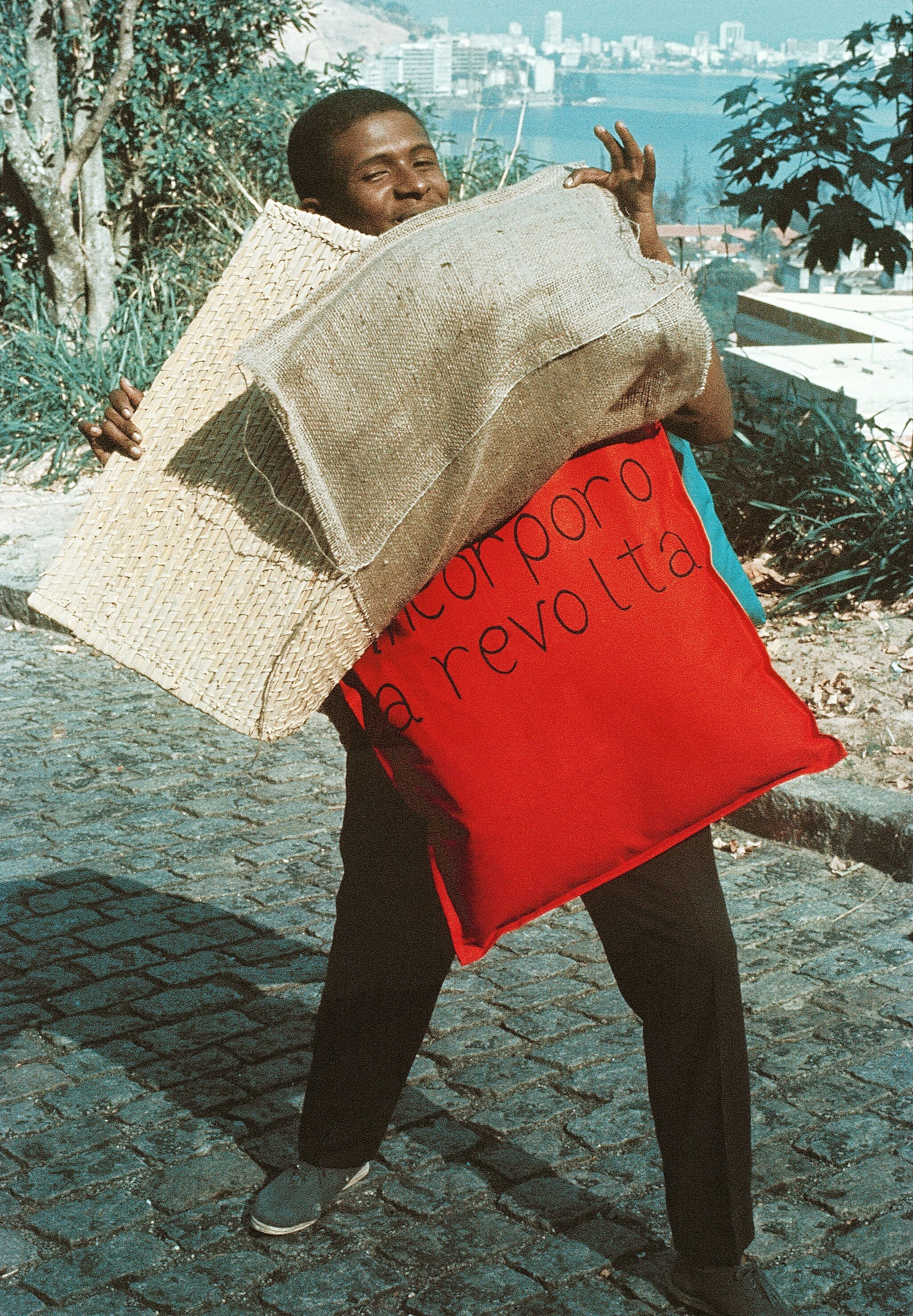 Image of man standing in street on hill overlooking body of water and holding burlap and pillows that say incorporo a revolta