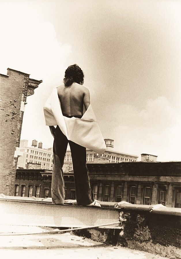 A man wears a white cape while standing on a rooftop with his back to the camera.