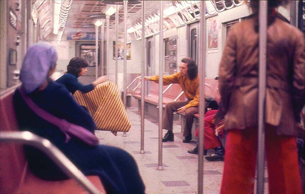 A group of people sit on a NYC subway.