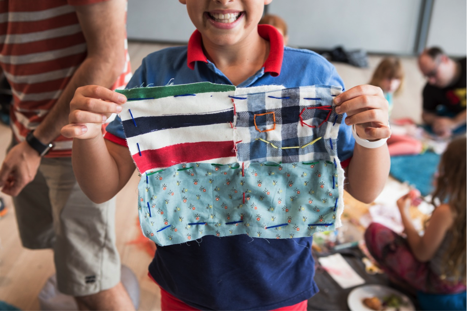 a child shows off their patchwork placemat