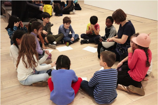 Students sit in a circle for a guided visit