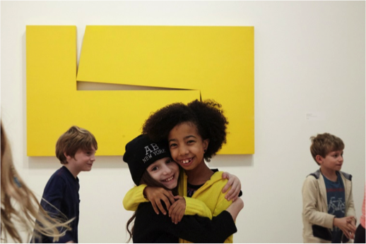 Students pose in the galleries in front of yellow work