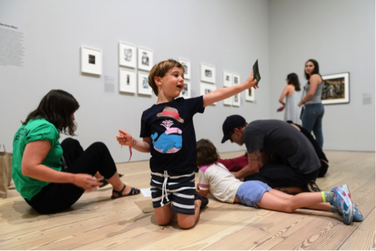 a young child shows off his art