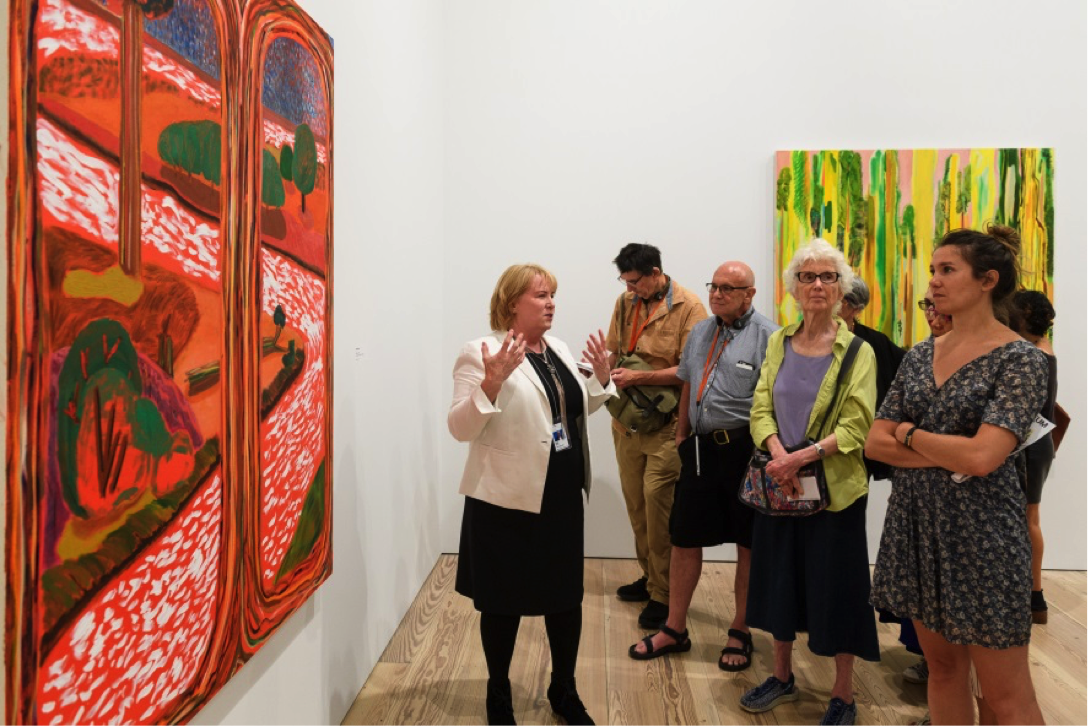 a docent discusses colorful paintings from the Biennial
