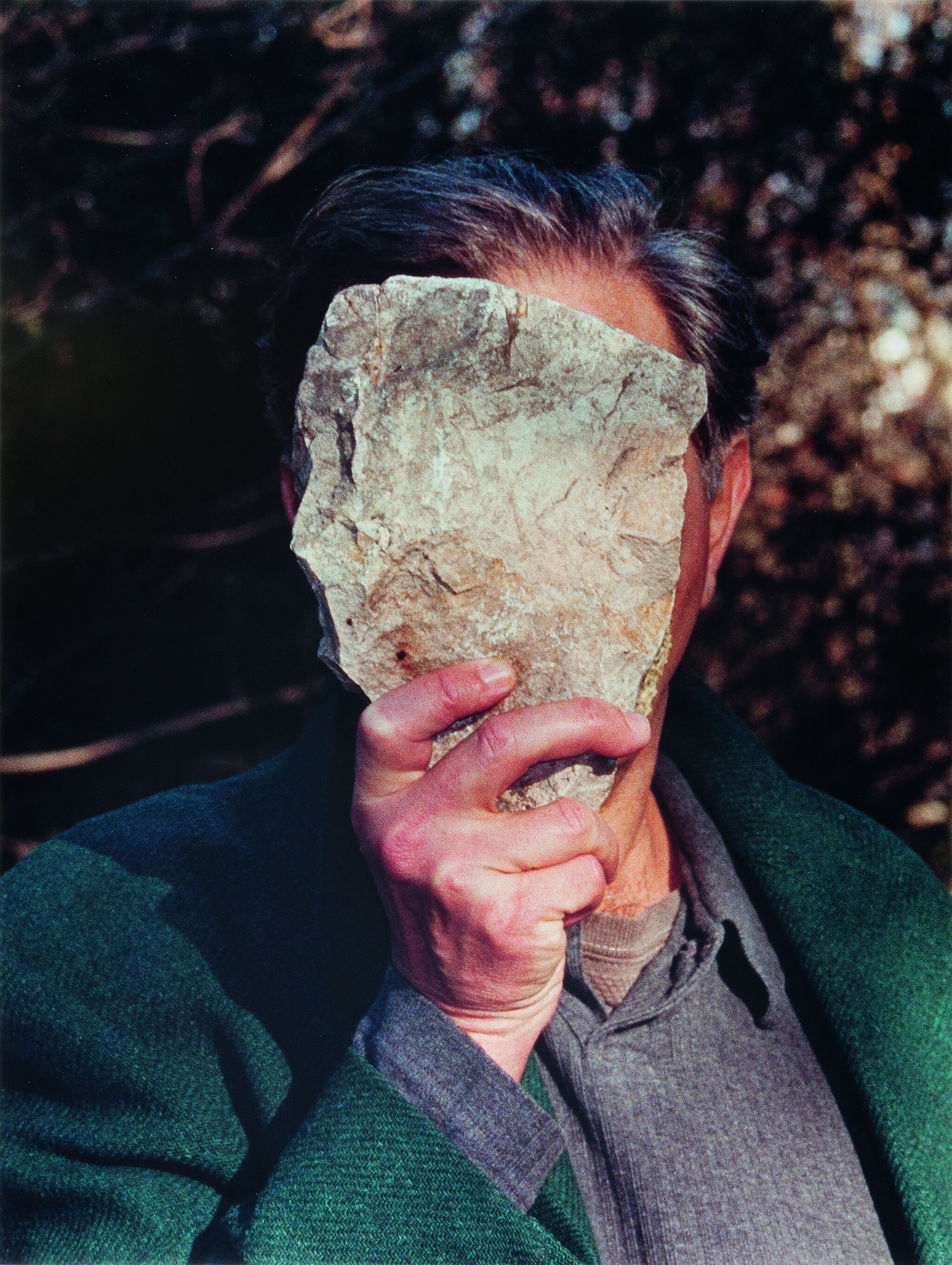 Photograph of a man holding a rock in front of his face.