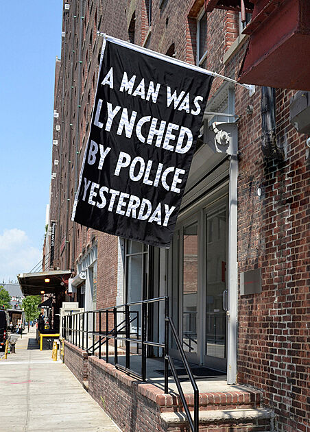 "A black flag with white text that says ""A Man Was Lynched by Police Yesterday."""