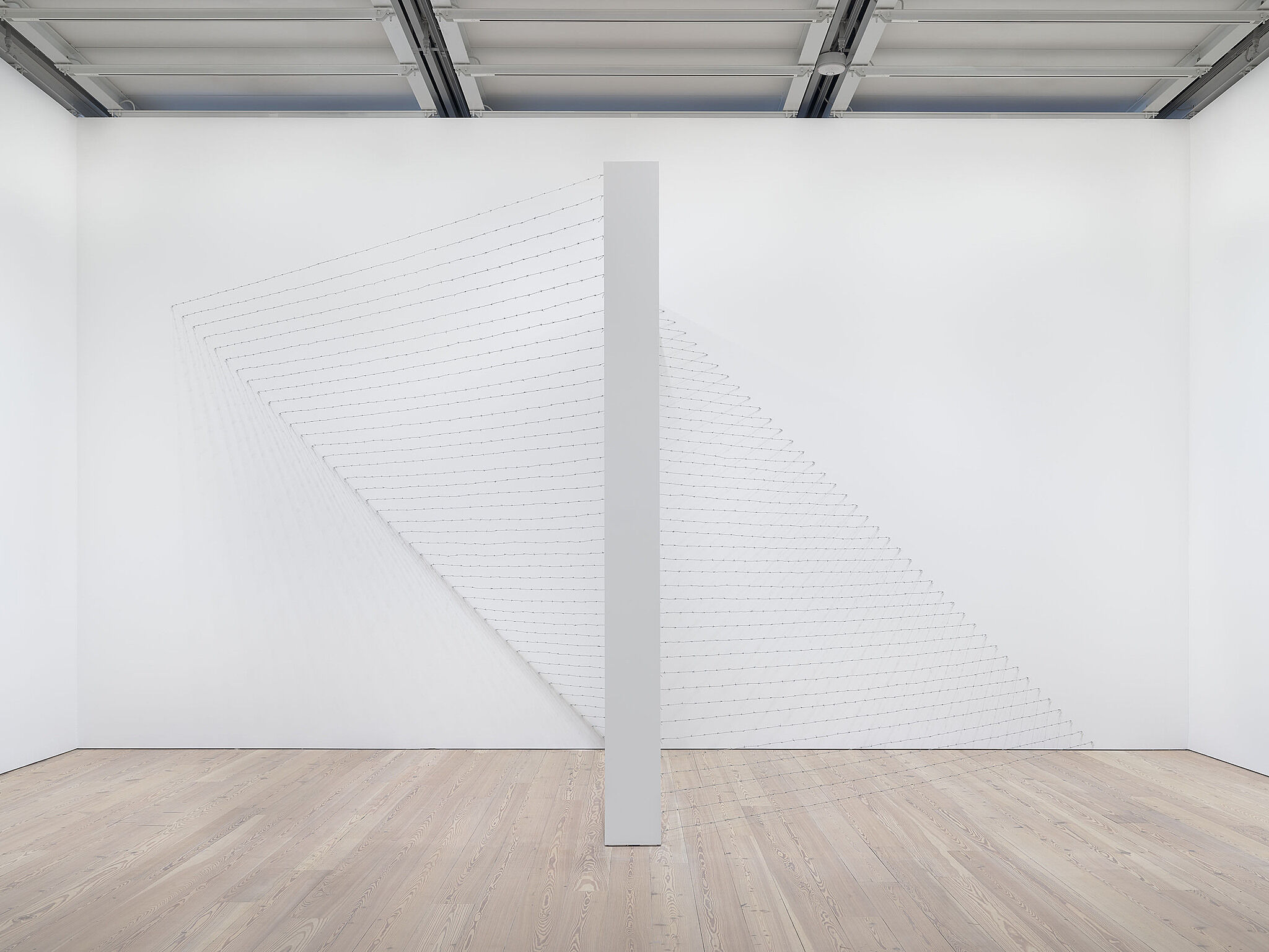Barbed wire spread across a white gallery, creating two pyramid shapes.