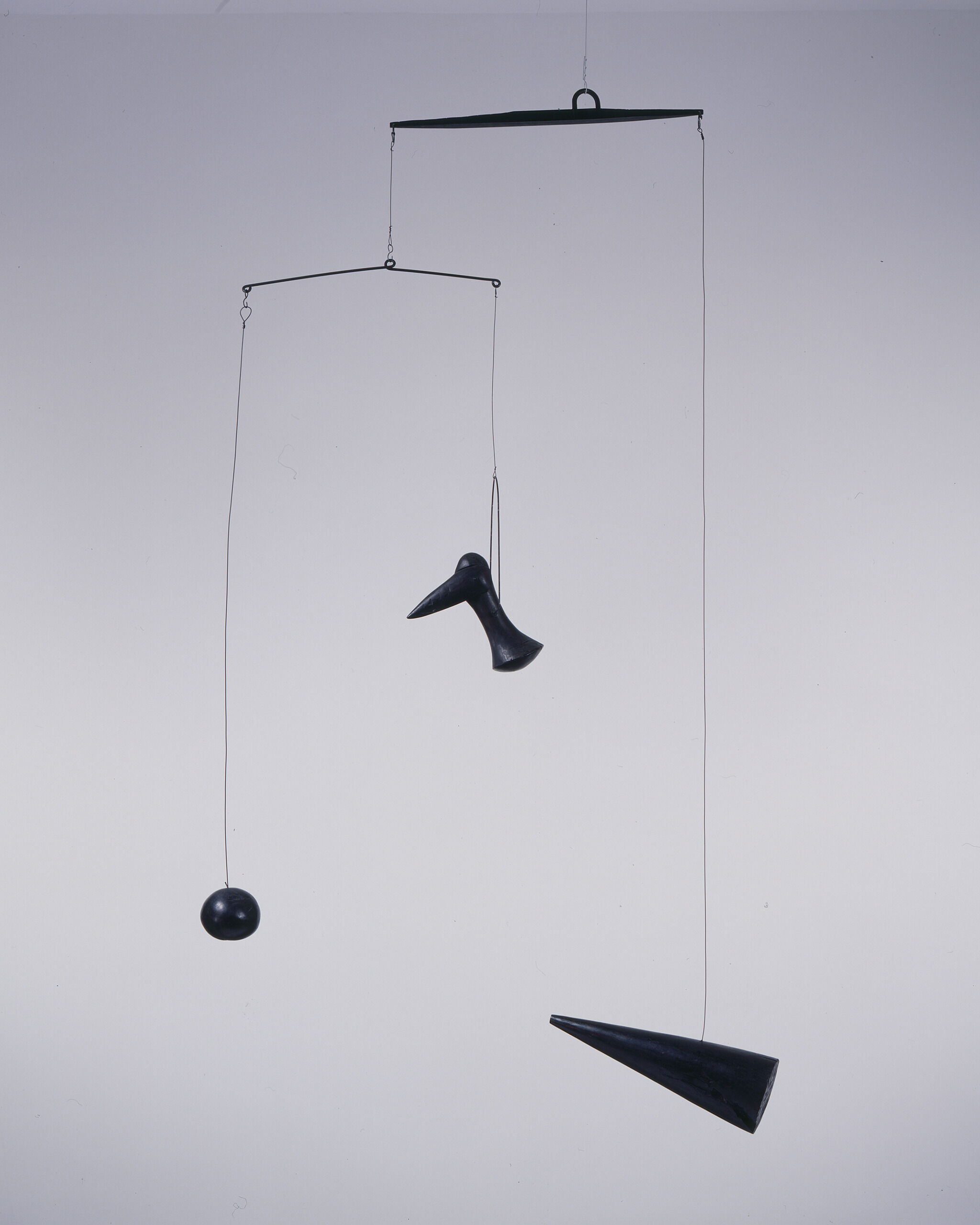 Three black objects hanging from a mobile.