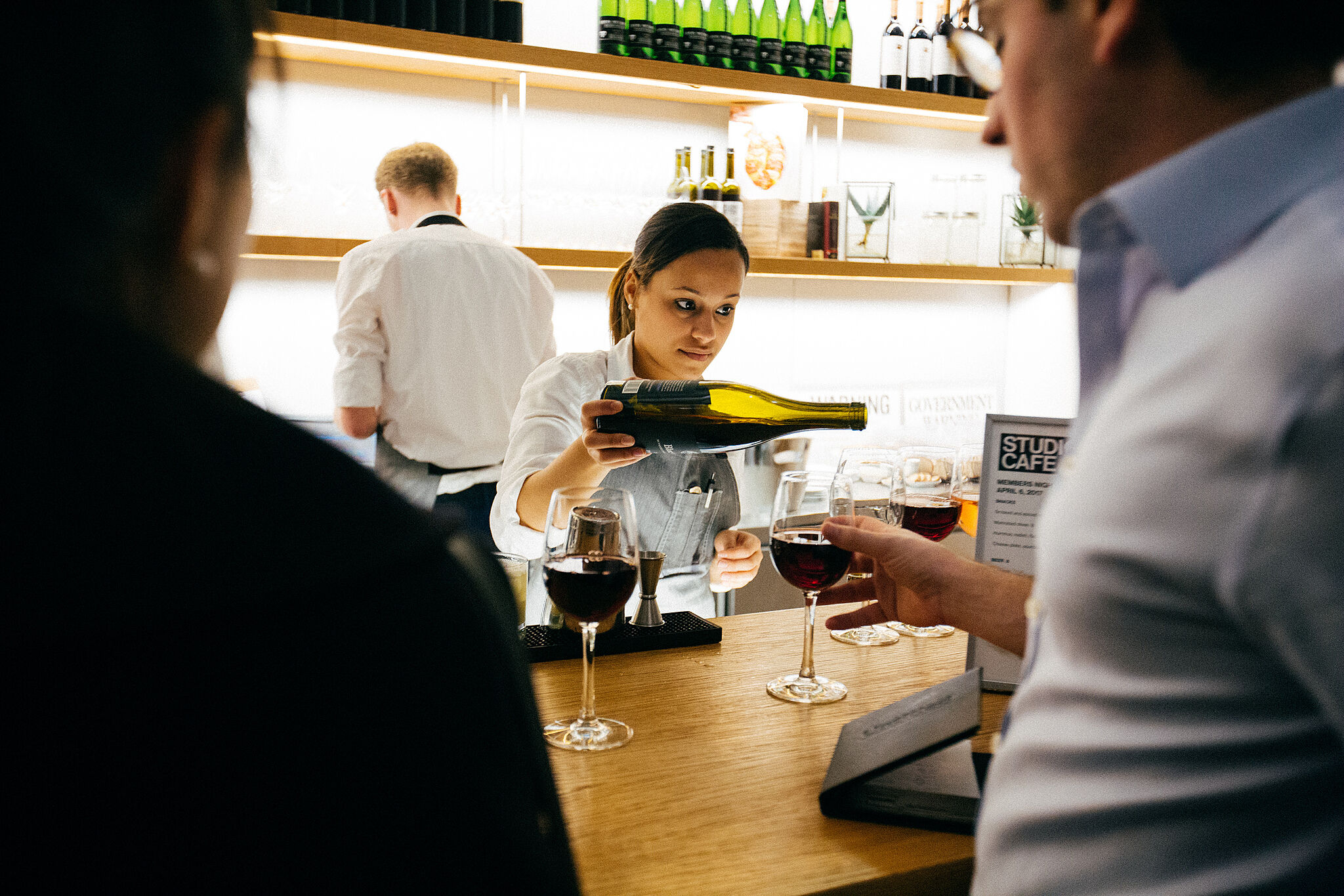 A woman pouring a bottle of wine at Studio Cafe.