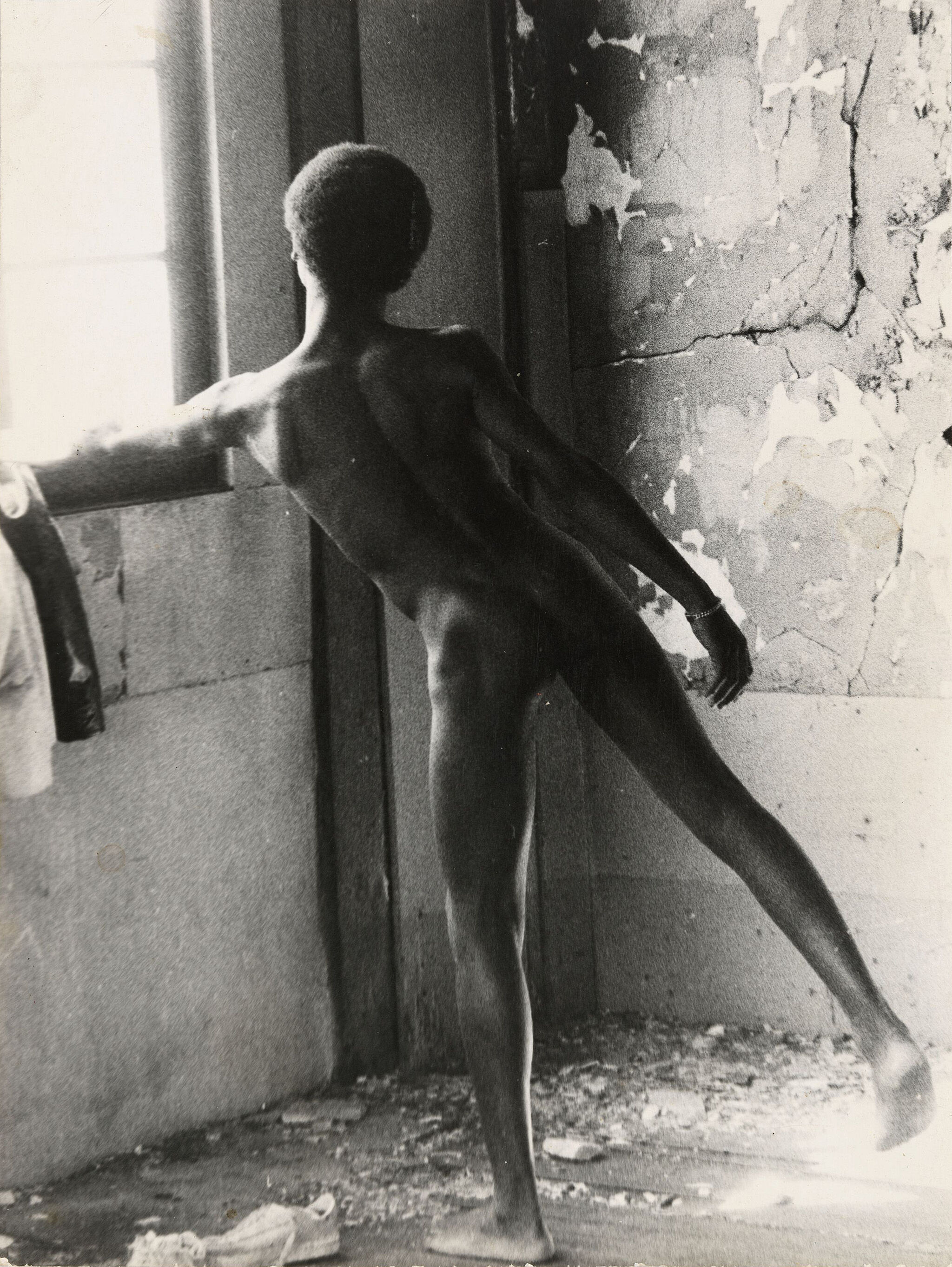 Black and white photograph of a nude person leaning on a window ledge.