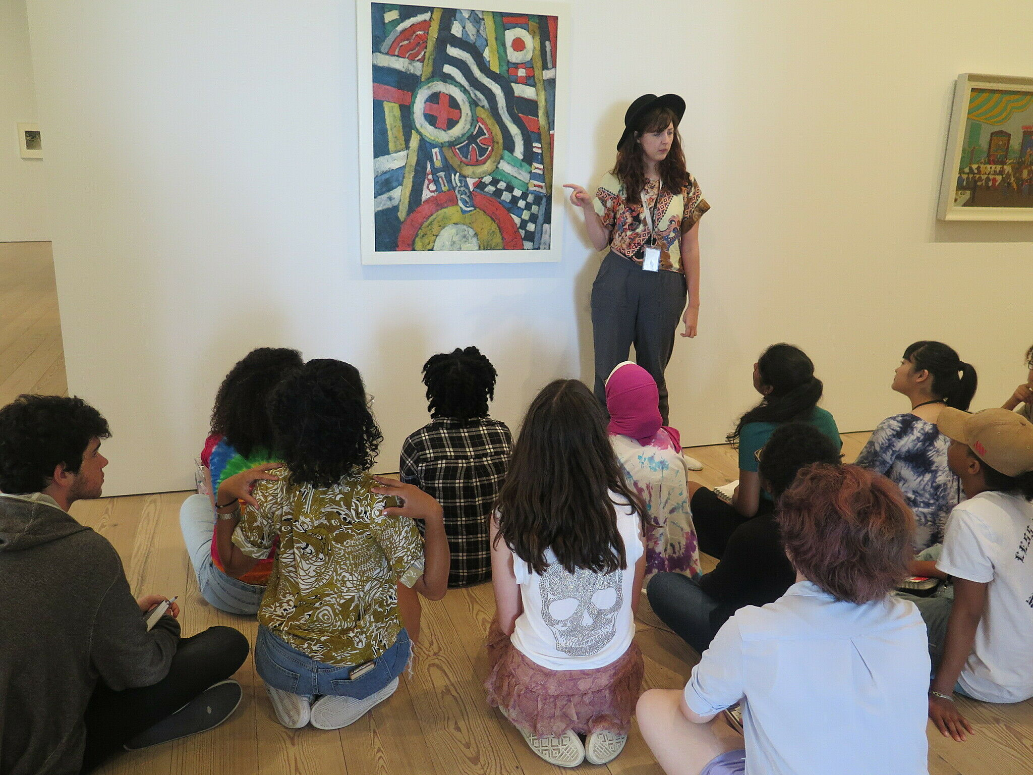 Billie Rae Vinson standing next to an artwork giving a talk