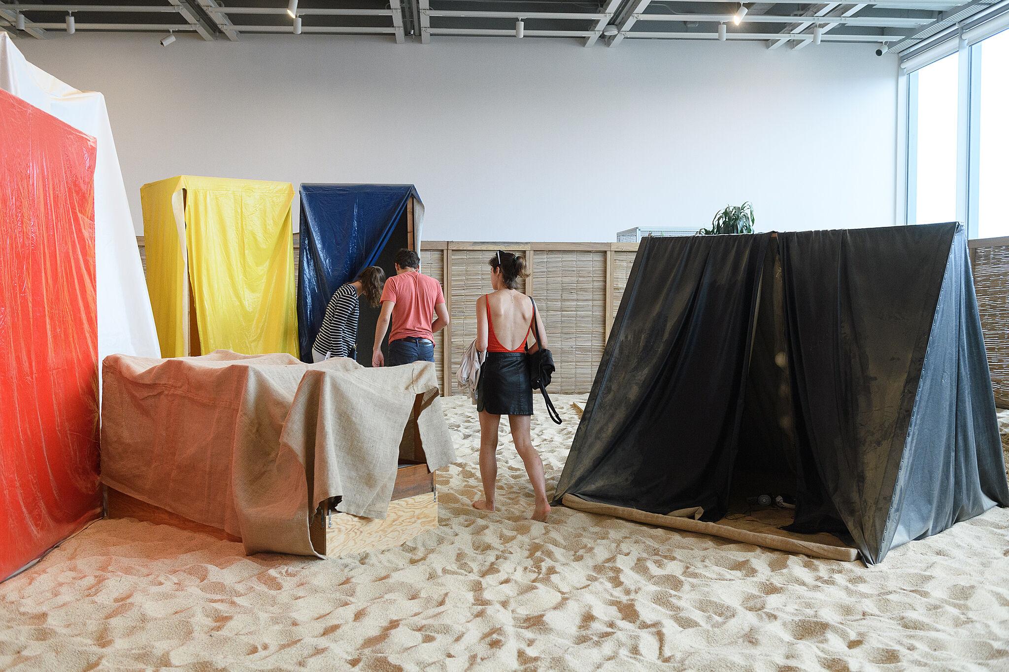Visitors walking through the Helio Oiticica exhibition