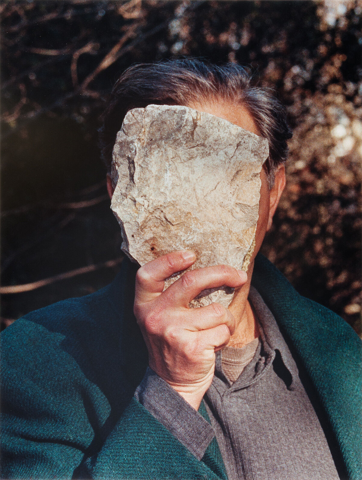 A man holding a stone in front of his face