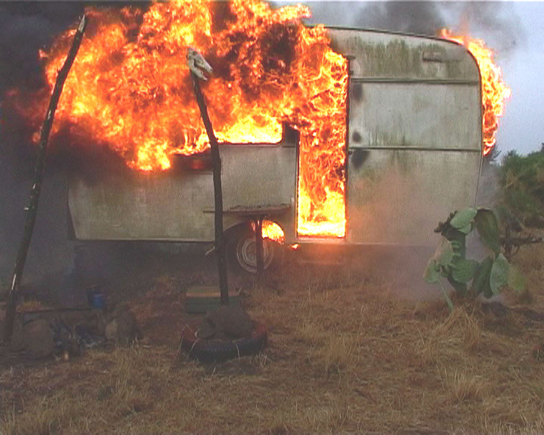 Film still of a burning van.