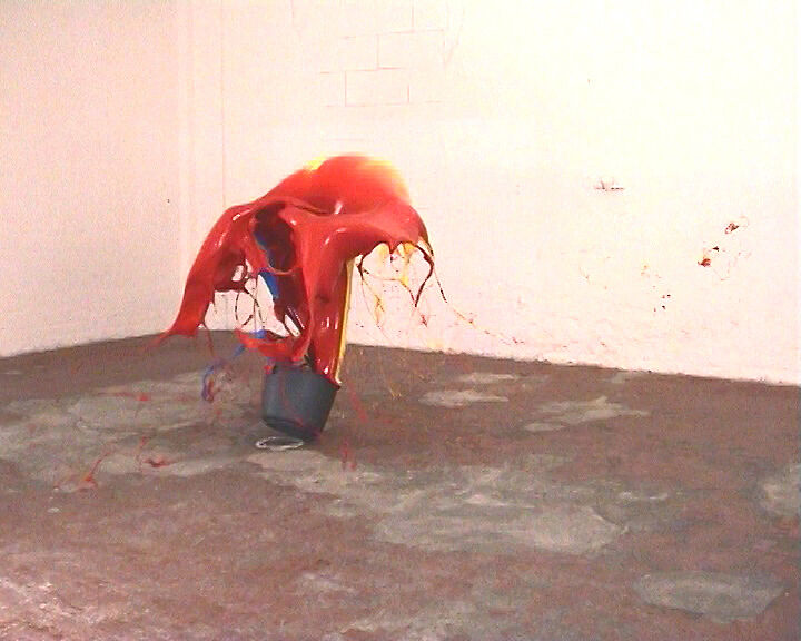Film still of a bucket with red liquid.