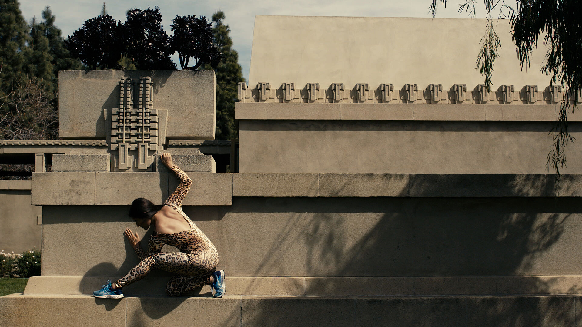 A woman in a leopard suit scaling a wall