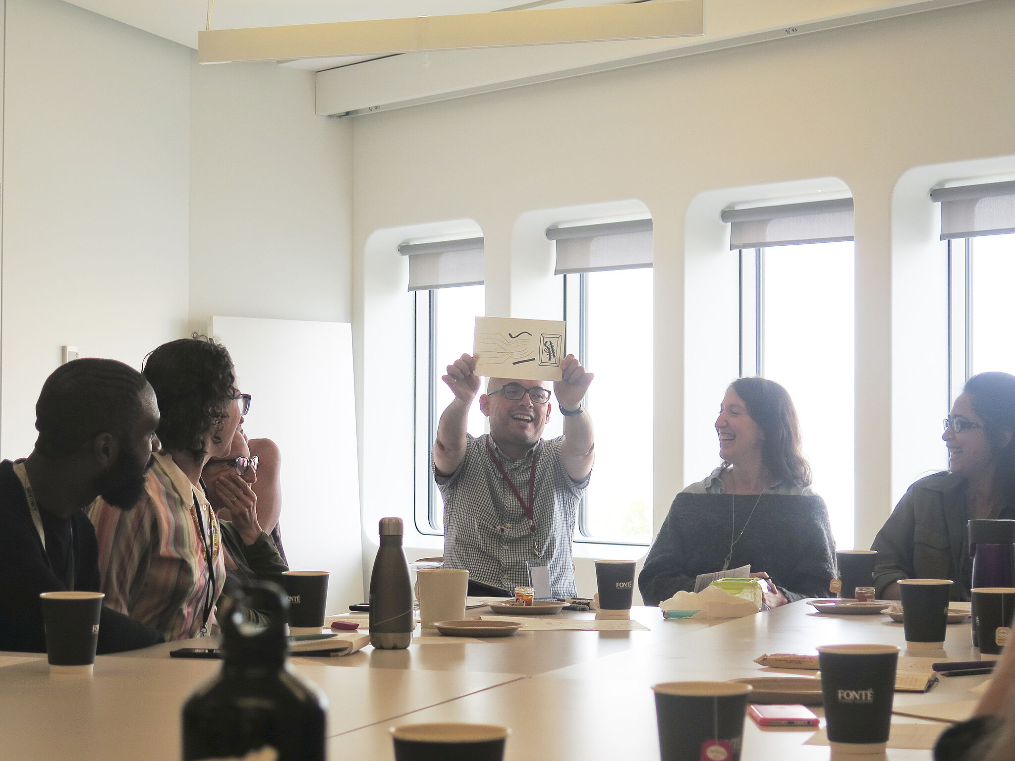 People sitting around a table with one person holding up a sheet of paper