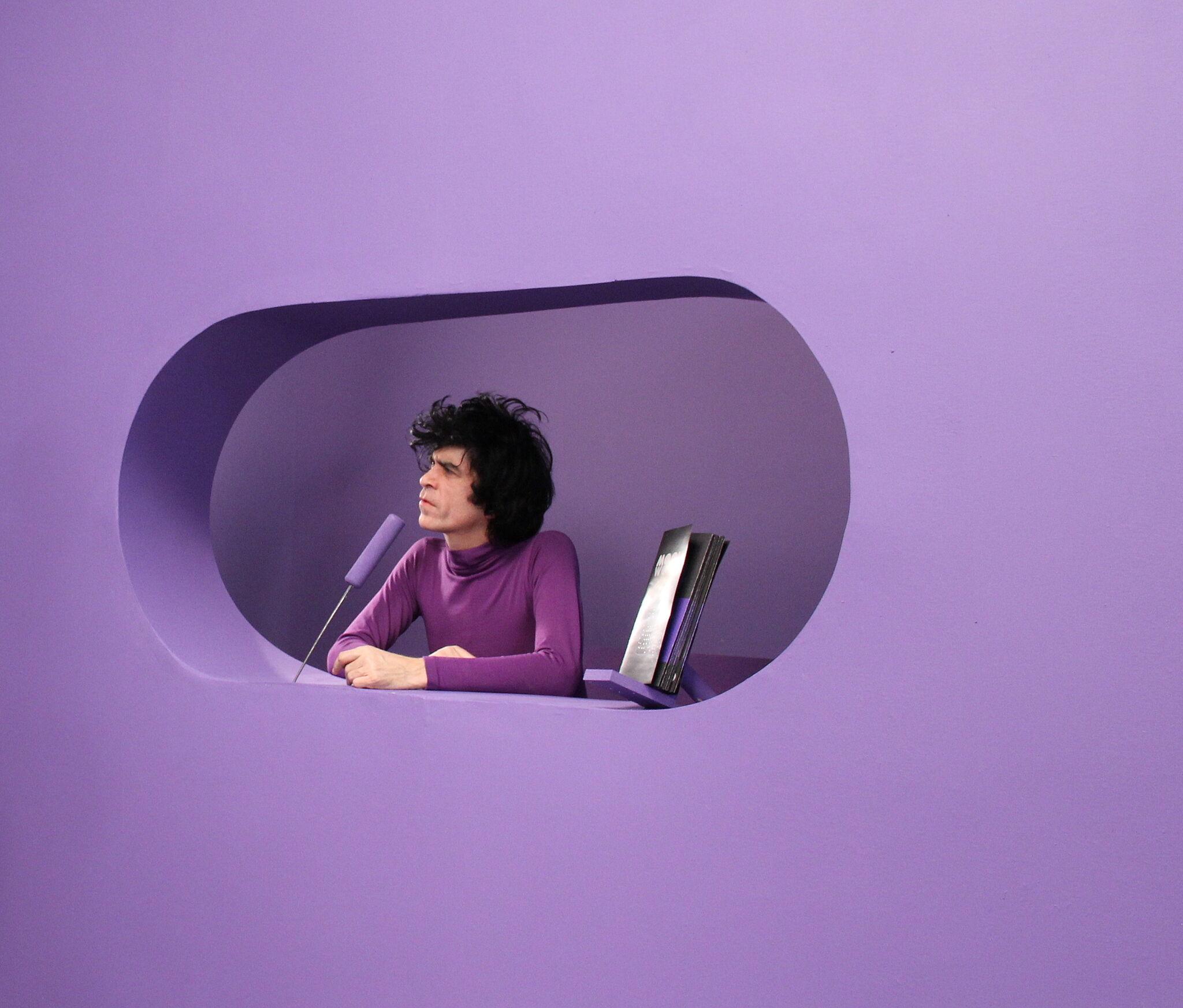 A man in purple in a purple room.