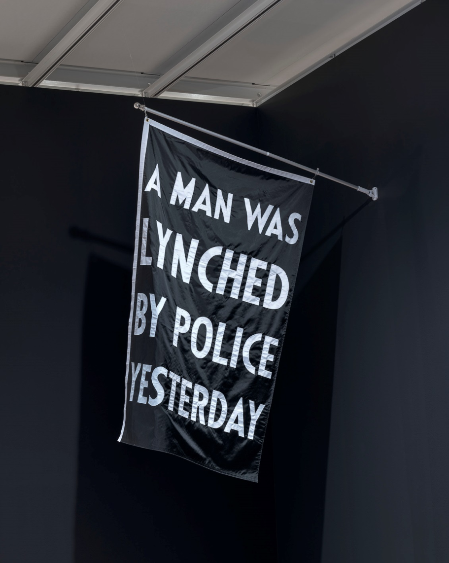"A banner that reads ""A man was lynched by police yesterday"""