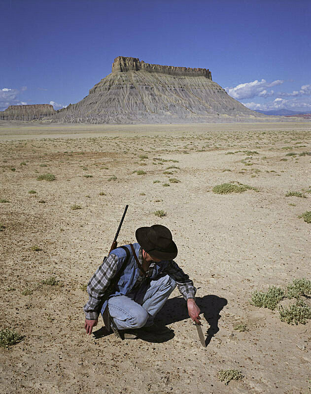 A man kneeling the in the desert, pressing his knife into the ground.