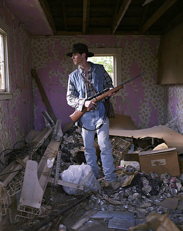 A man holding a rifle in a room on top of a pile of trash.
