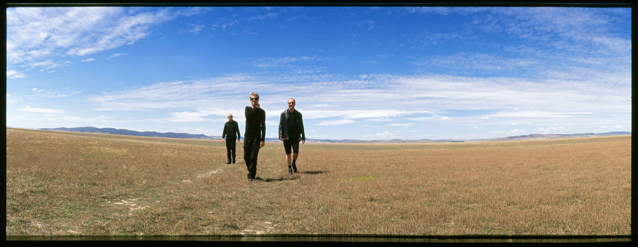 Three men standing in a barren field of short grass walking towards the camera.