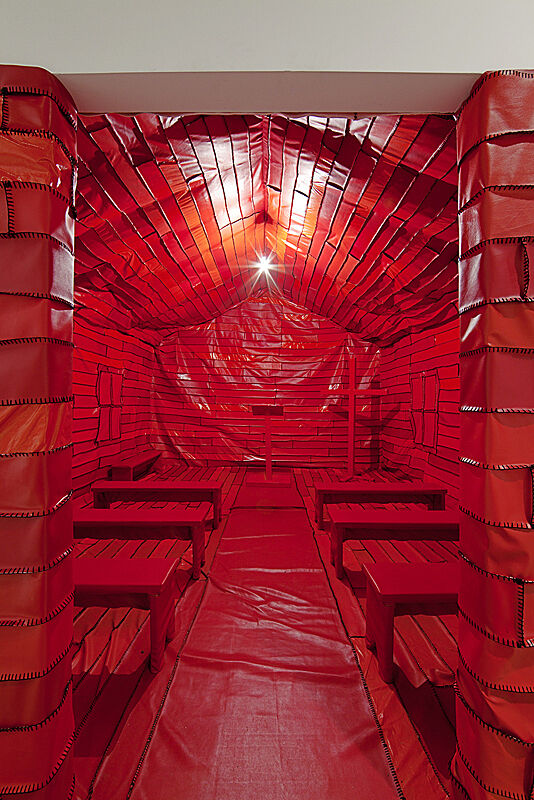 Installation photograph of Blues for Smoke exhibition. Image depicts a all-red replication of the interior of a chapel.