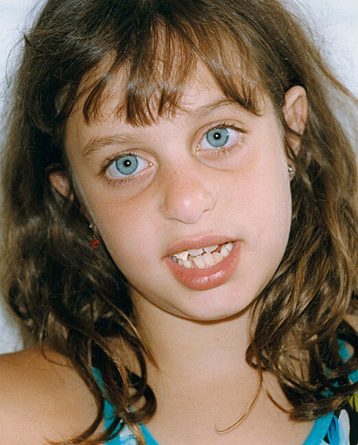 Close up photograph portrait of young girl with blue eyes and chewing gum in her mouth.