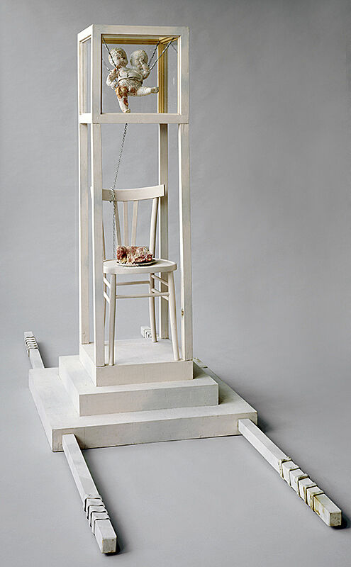 Tall wooden sculpture painted white with small chair, a bouquet of flowers and a porcelain statue of two children.