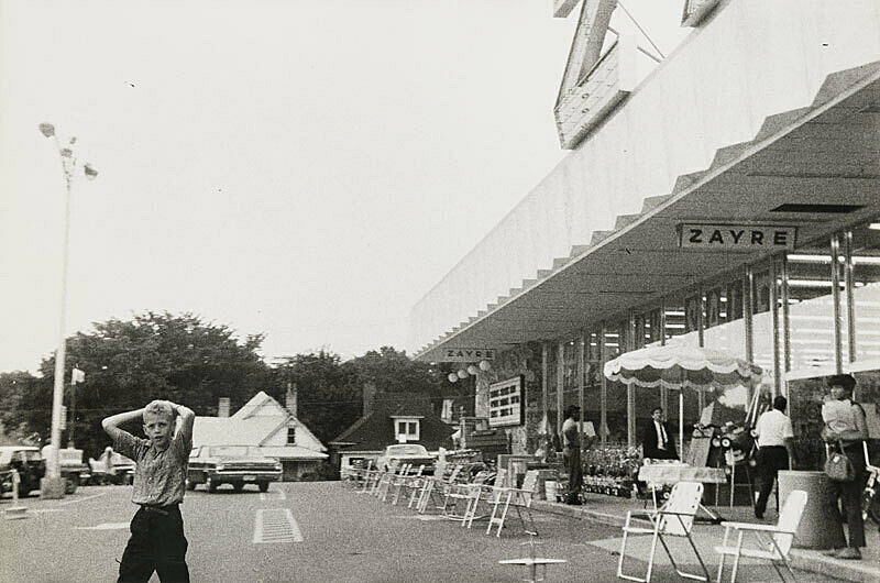Black and white photograph of parking lot with lawn chairs lining the side walk and a young boy facing camera.