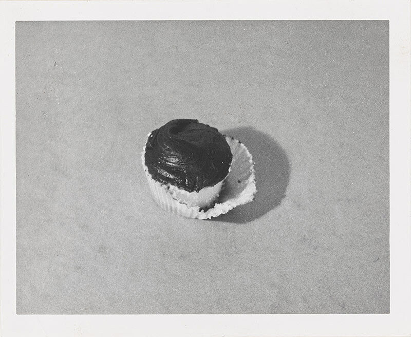Black and white photograph of frosted cupcake.