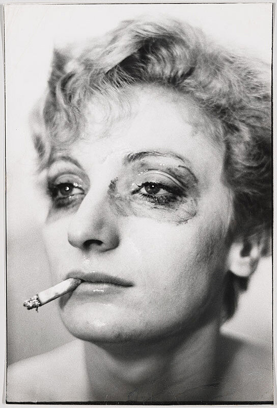 Close up portrait photograph of a woman smoking a cigarette with makeup smeared around her eyes.