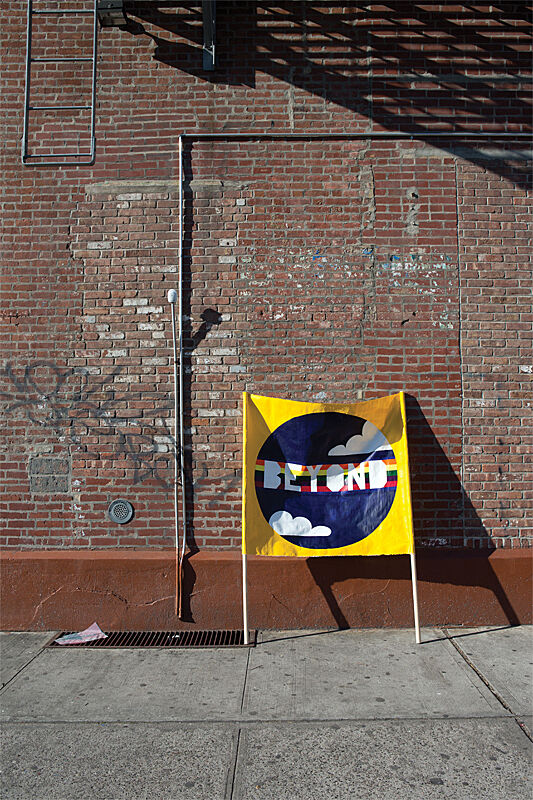 "Image of yellow banner with the word ""beyond"" written over a rainbow graphic. The banner leans against a brick wall with graffiti on it."