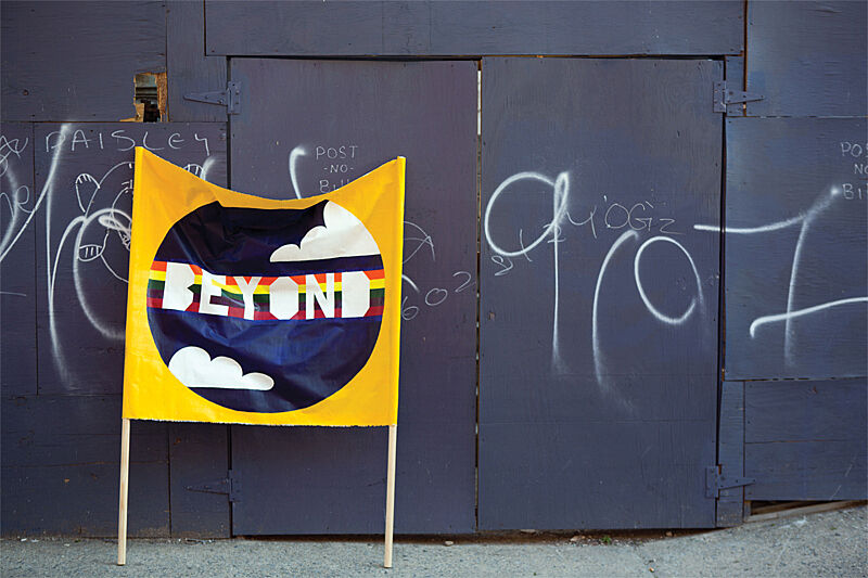 "Image of yellow banner with the word ""beyond"" written over a rainbow graphic. The banner leans against a broken-down purple wall with graffiti on it."
