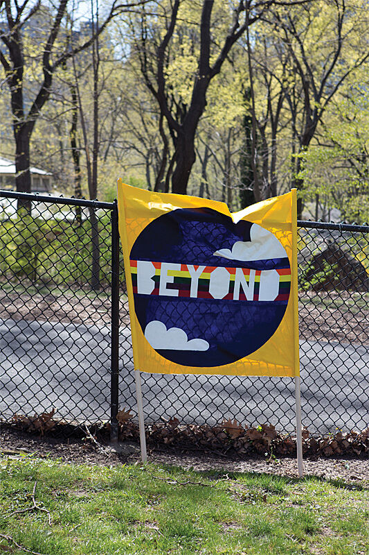 "Image of yellow banner with the word ""beyond"" written over a rainbow graphic. The banner leans against a fence with tall trees in the background."