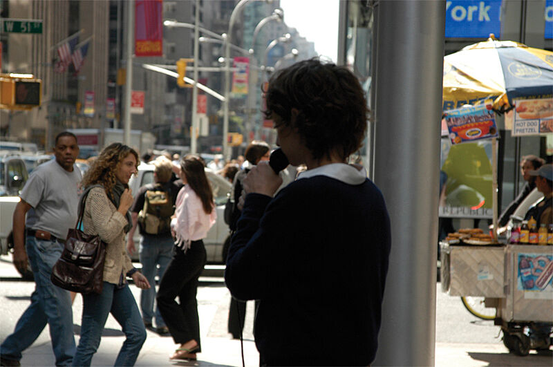 Photograph of a person with a microphone speaking on a busy sidewalk in New York City.