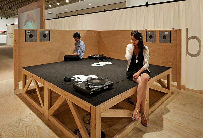 Woman and man sit listening to record turntable installation at Sharon Hayes There's so much I want to say to you exhibition.