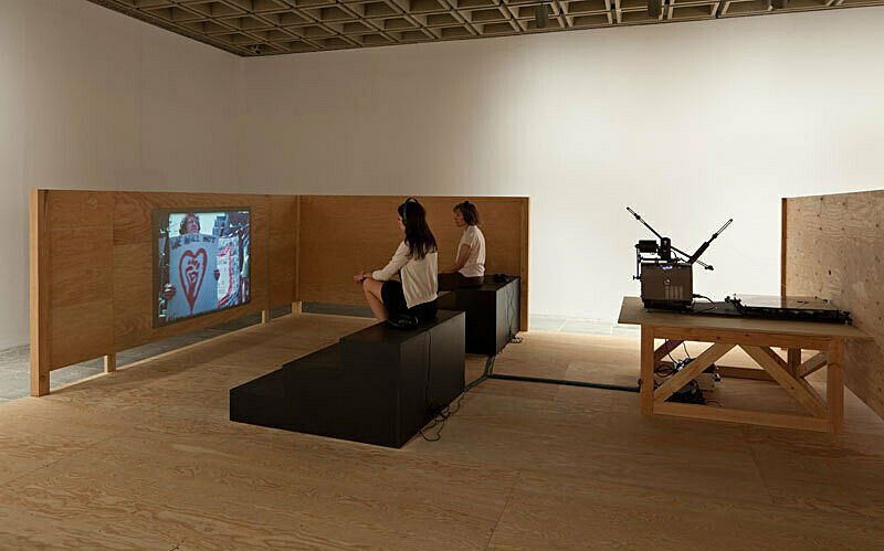 Woman and man sit watching video installation at Sharon Hayes There's so much I want to say to you exhibition.