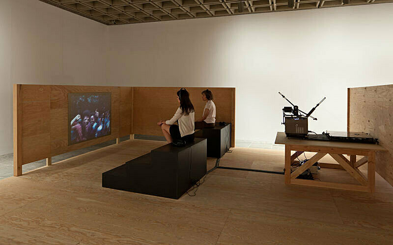 Man and woman sit watching video installation at Sharon Hayes There's so much I want to say to you exhibition.