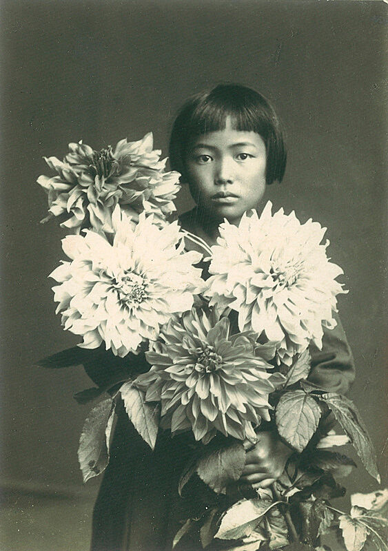 Portrait of Yayoi Kusama at age ten, holding flowers.